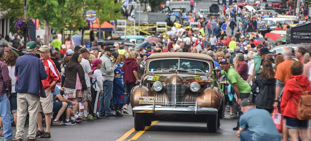 A 1941 Cadillac pulls through the crowd in Fairport, NY.jpg