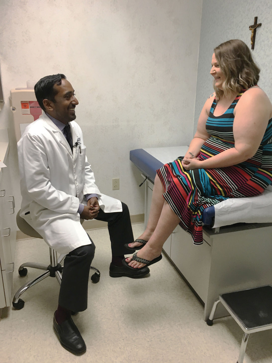 Rudy Malayil, MD, talks with patient, Cara Spencer.