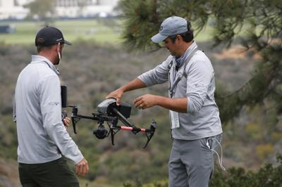 Drone operator Ben McClung picks up a drone used for coverage of the U.S. Open at the Torrey Pines Golf Course on Wednesday, June 16, 2021 in La Jolla, Calif. Tanner Deprin, left, looks on.