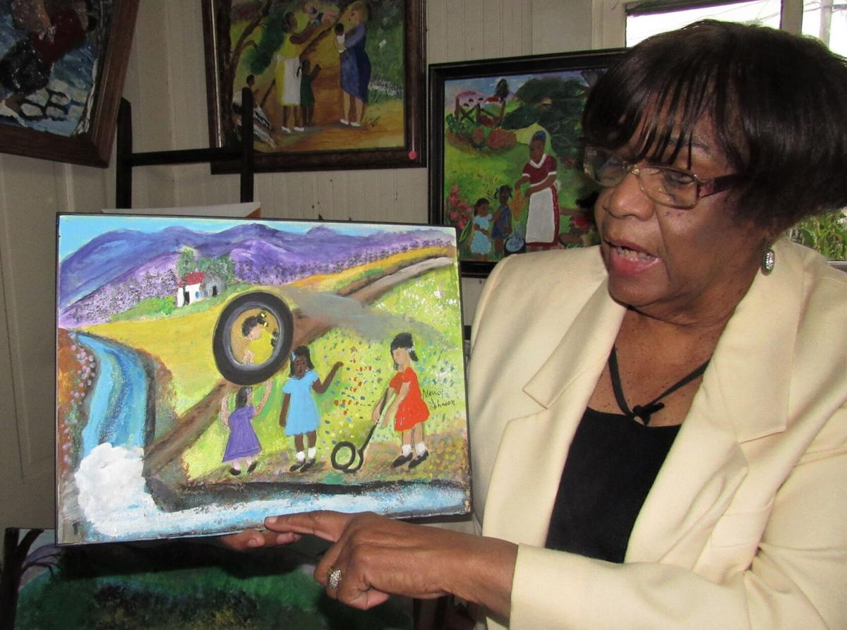 2, Nancy holding painting of children playing games