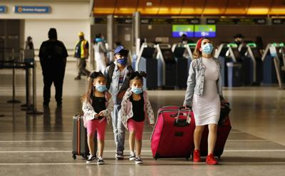 Yadira Barajas walks with her children Owen Vargas, 11, and 6-year-old twins Madison and Madelyn Contreras, as they prepare for a flight to Mexico at Tom Bradley International Terminal at Los Angeles International Airport, which is requiring travelers to wear face coverings to help keep fellow passengers and crew safe by limiting the spread of the coronavirus COVID-19, on May 11, 2020.