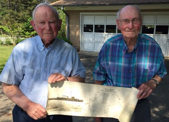 Harley and James hold a picture of the Tatum, Harley's ship during the war.jpg