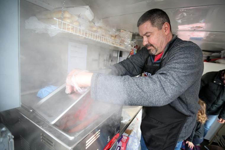 Mike Deck makes a specialty hot dog