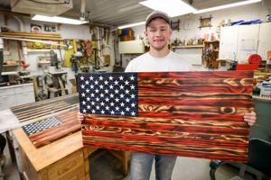 """<p class=""""p1"""">Nathan McClenahen holds a pine U.S. flag he built for a customer. The 20-year-old North Dakota State University student has built around 20 flags so far.</p>"""