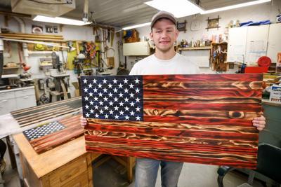 Nathan McClenahen holds a pine U.S. flag