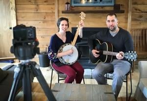 "<p class=""p1"">Amanda Johnson and her husband, Our Savior's Lutheran Church Pastor Joe Johnson, pose in front of their digital camera, used to record their fireside services on Facebook and YouTube.<span class=""Apple-converted-space""> </span></p>"