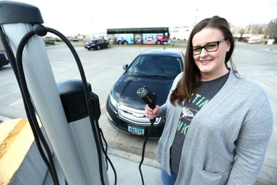 Mary Matton poses in front of the new EV charging station