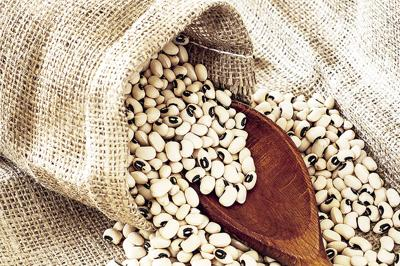 Black eyed peas in jute bag spilled on jute background with wooden spoon