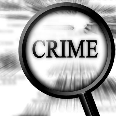 Crime - news paper with magnifier over the word crime