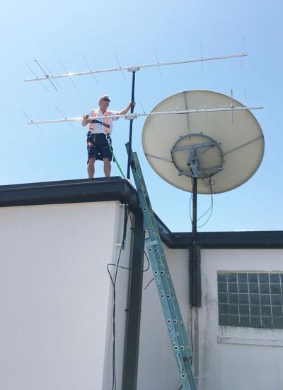 Steve Alfano installing bird tracking antenna at Vero Beach High School