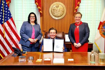 Rep. Erin Grall with Gov. DeSantis at signing of anti-abortion law
