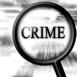 crime - magnifier over newsprint magnifying the word crime