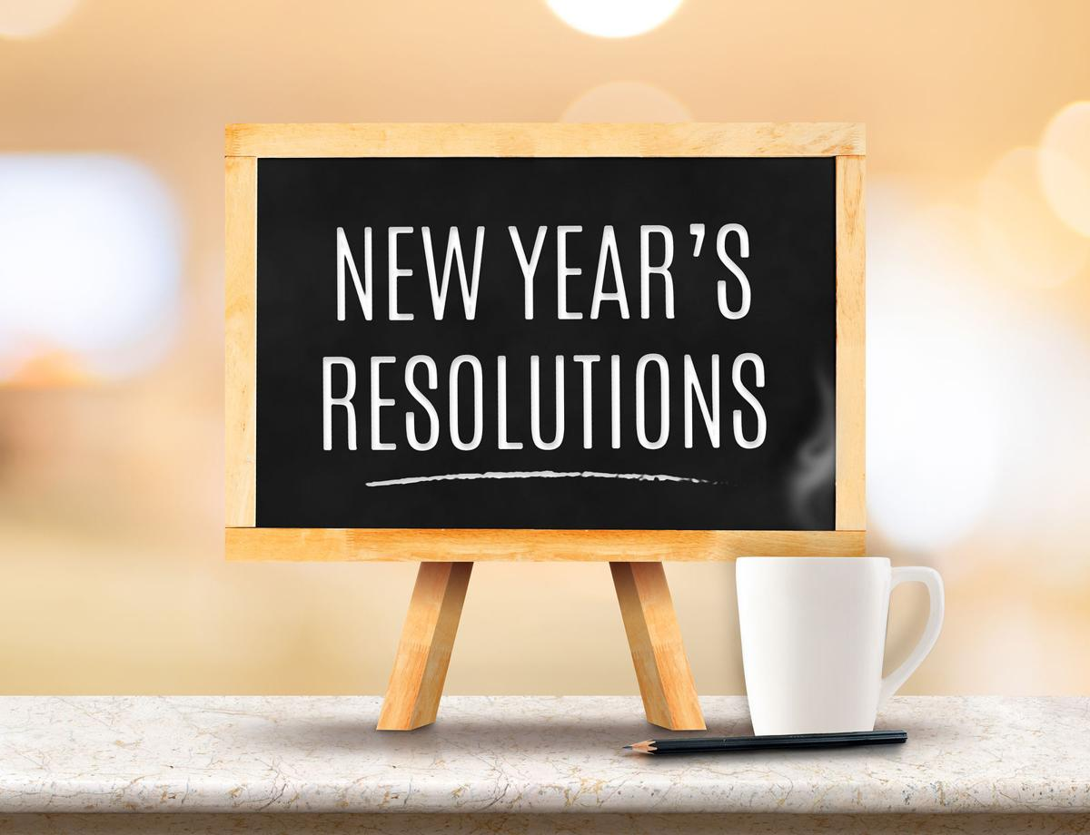 New Year's Resolutions Word On Blackboard With Easel On Marble Table Top With Sun And Blur Abstract