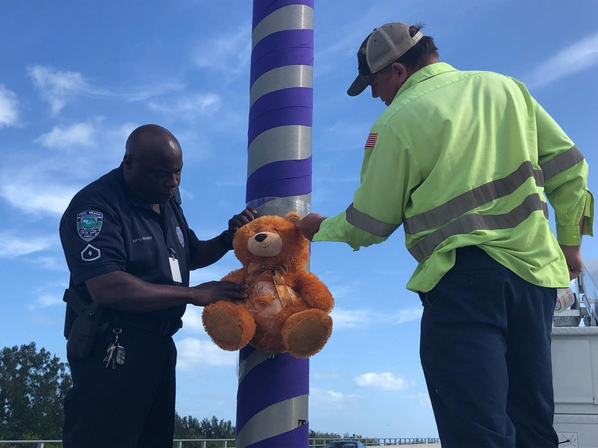 VBPD Officer Darrel Rivers wraps purple ribbons around light poles on the Barber Bridge