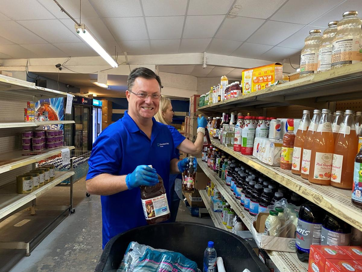 Cleveland Clinic Indian River Hospital President Dr. Greg Rosencrance stocking shelves at the UP Center member share grocery