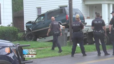 Police investigating car vs. house crash.jpg