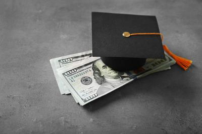 Graduation hat and dollar banknotes on table. Tuition fees concept