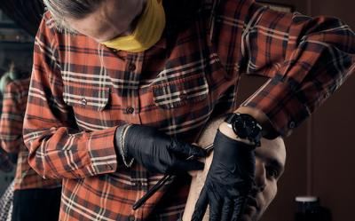 Male hairdresser in a protective mask and gloves, dressed in casual clothes. Client without a mask. Hairdressing after quarantine. Health precautions. Small business. Coronavirus pandemic aftermath.