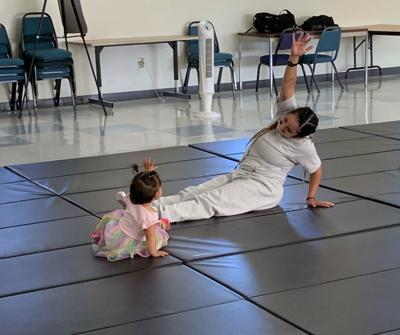 mother does stretches alongside her young daughter