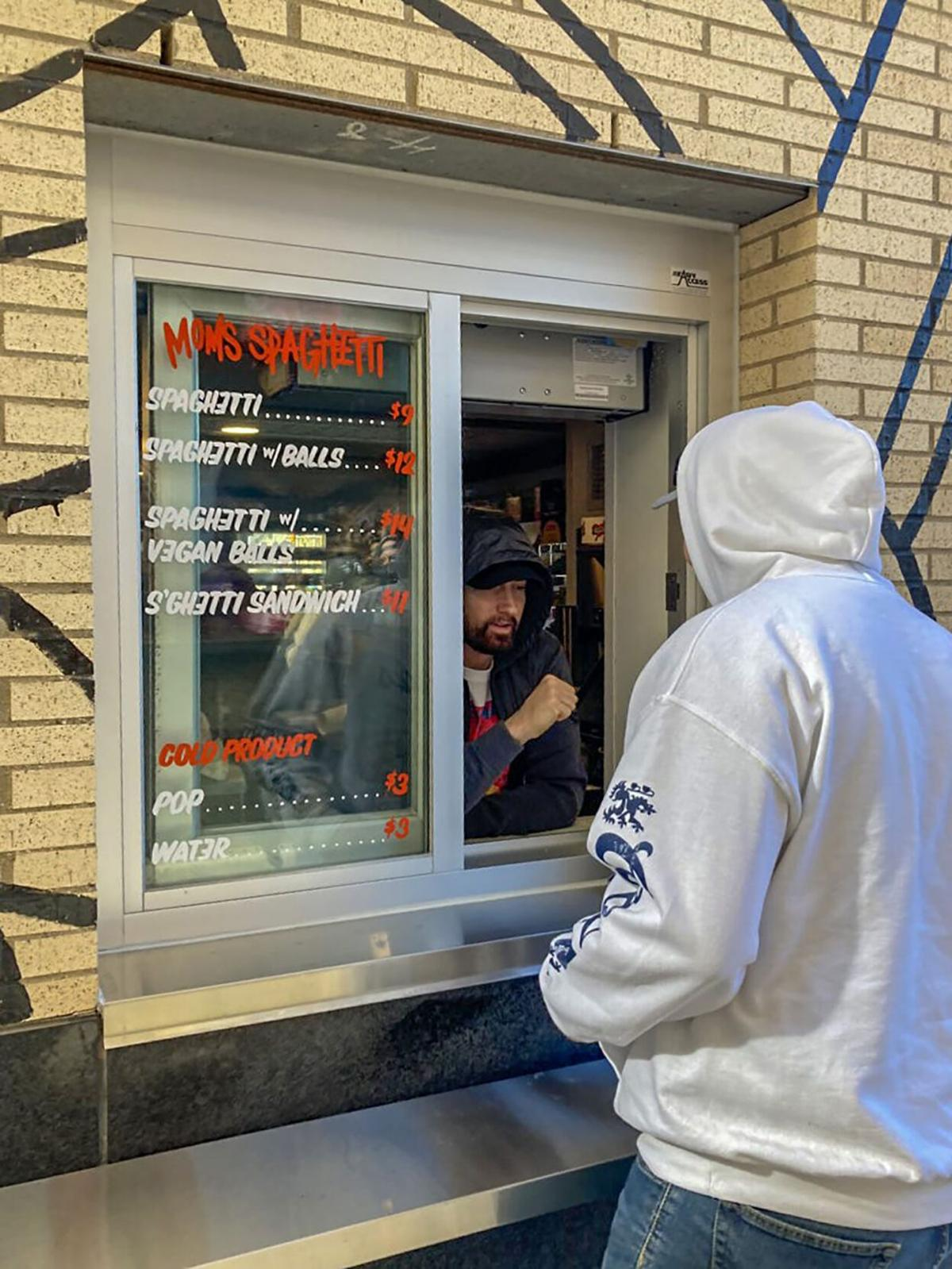 Eminem greets a patron at the window of Mom's Spaghetti on Wednesday, Sept. 29, 2021, in Detroit.