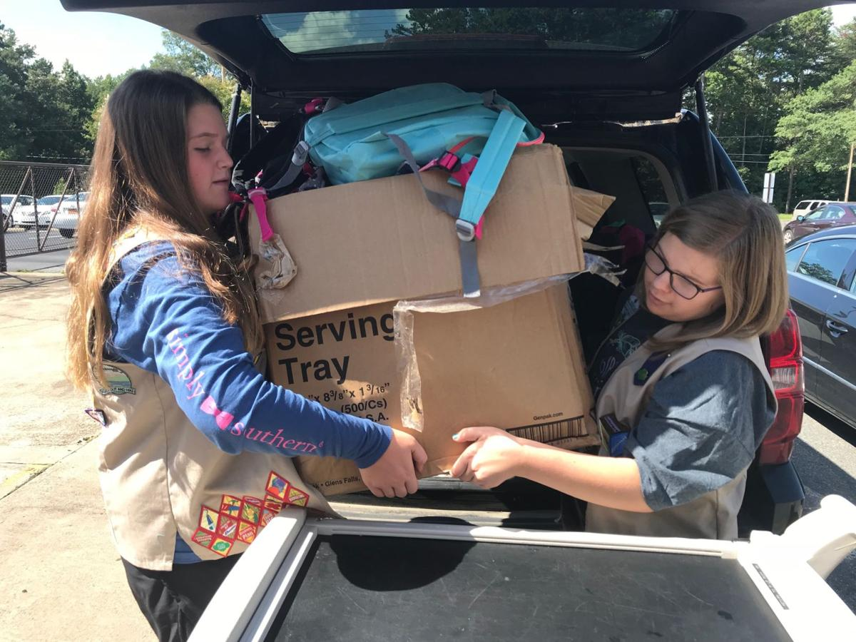 helping hands two girl scouts load backpacks for foster students news. Black Bedroom Furniture Sets. Home Design Ideas