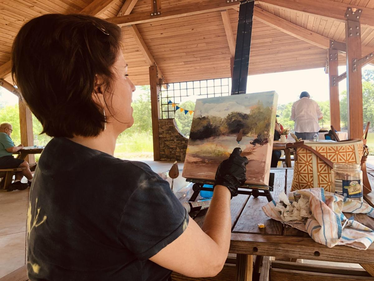 Alice Lewis works on a landscape painting at the pavilion at Grace Street Park