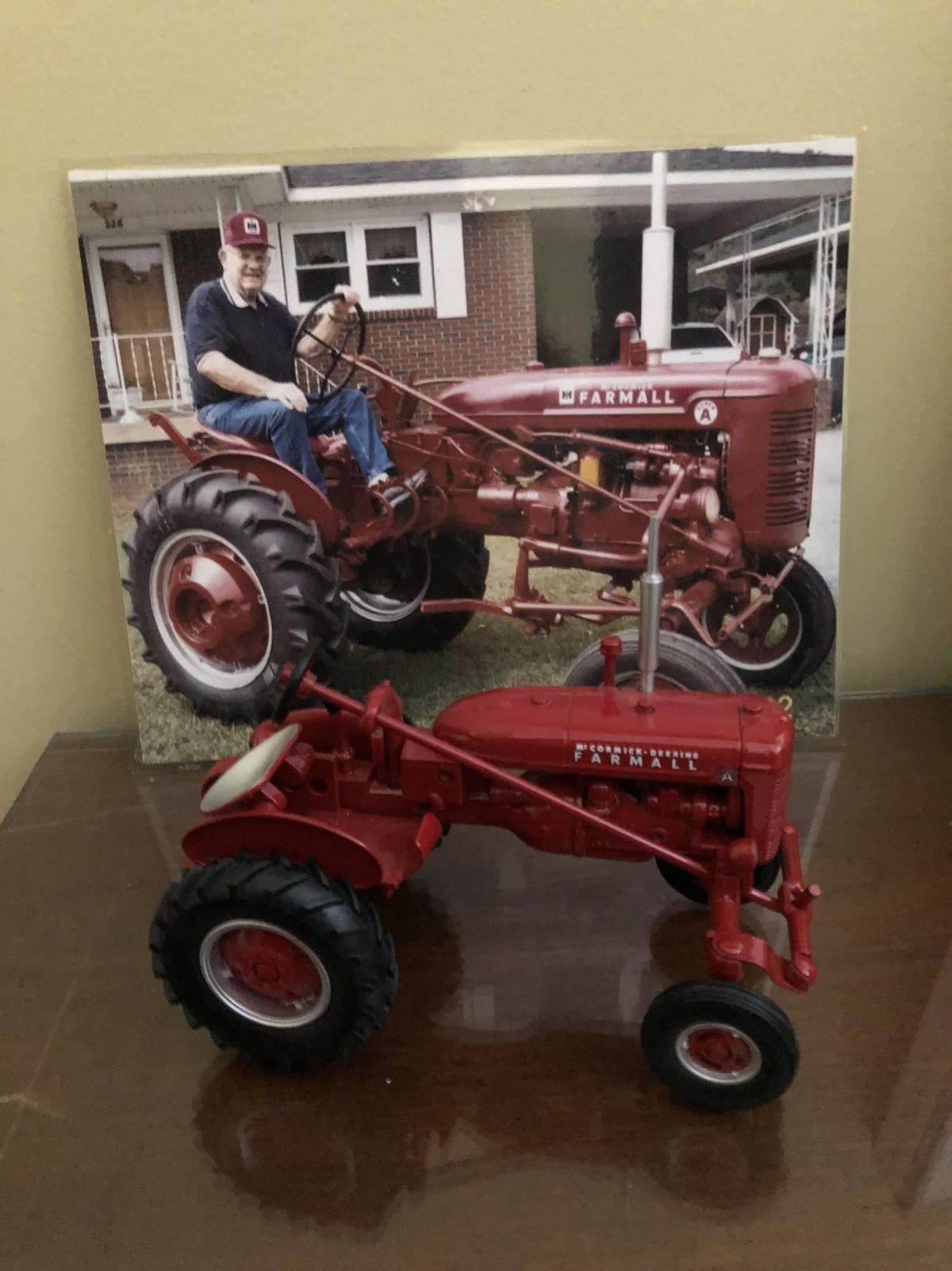 A photo of Ray Kidd on his restored Farmall tractor and a die-cast model of a Farmall