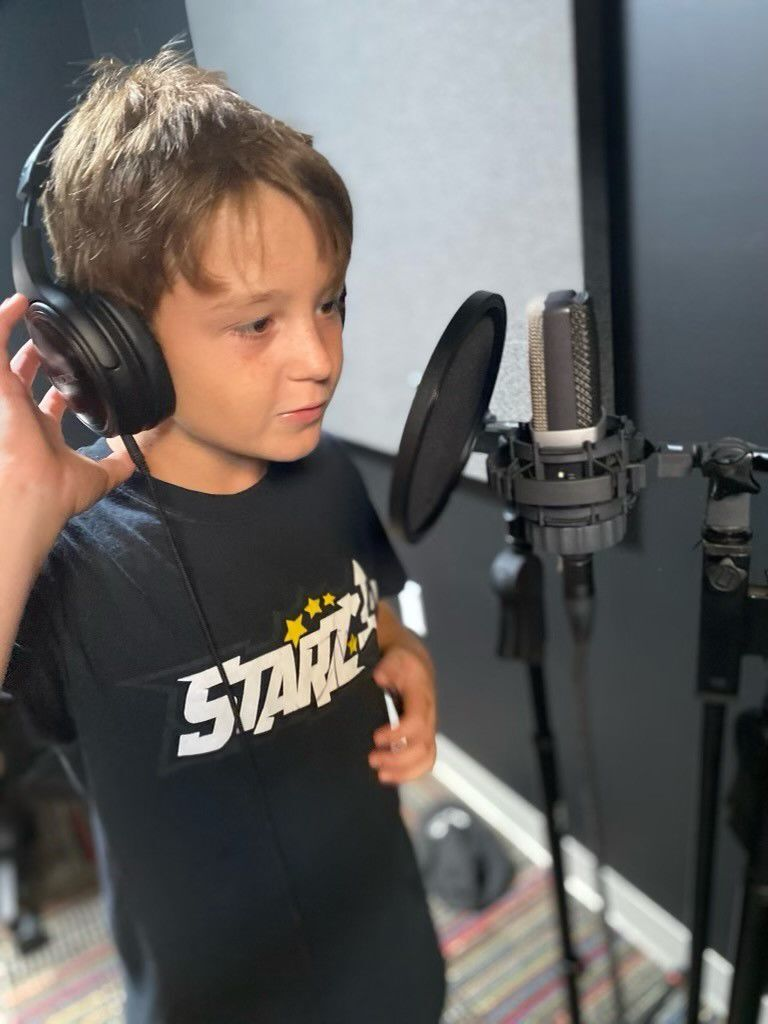 Benjo Smith, 9, laying down vocals at the Starz 24 Teen Center recording studio in Greenwood