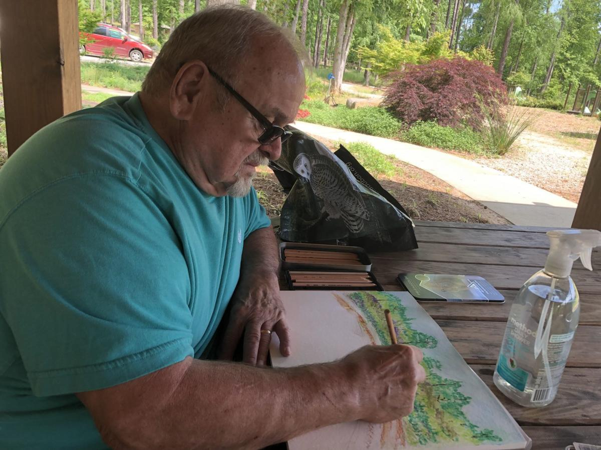 Rick Goohs uses watercolor pencils to create his landscape during a plein-air day