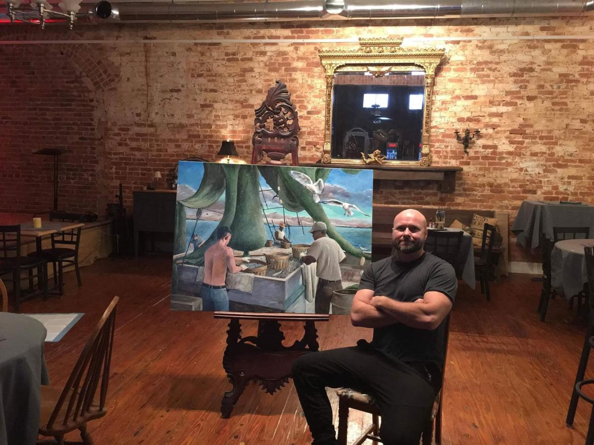 Painter Judson Arce at Natty's in Abbeville with a painting of shrimp boat life