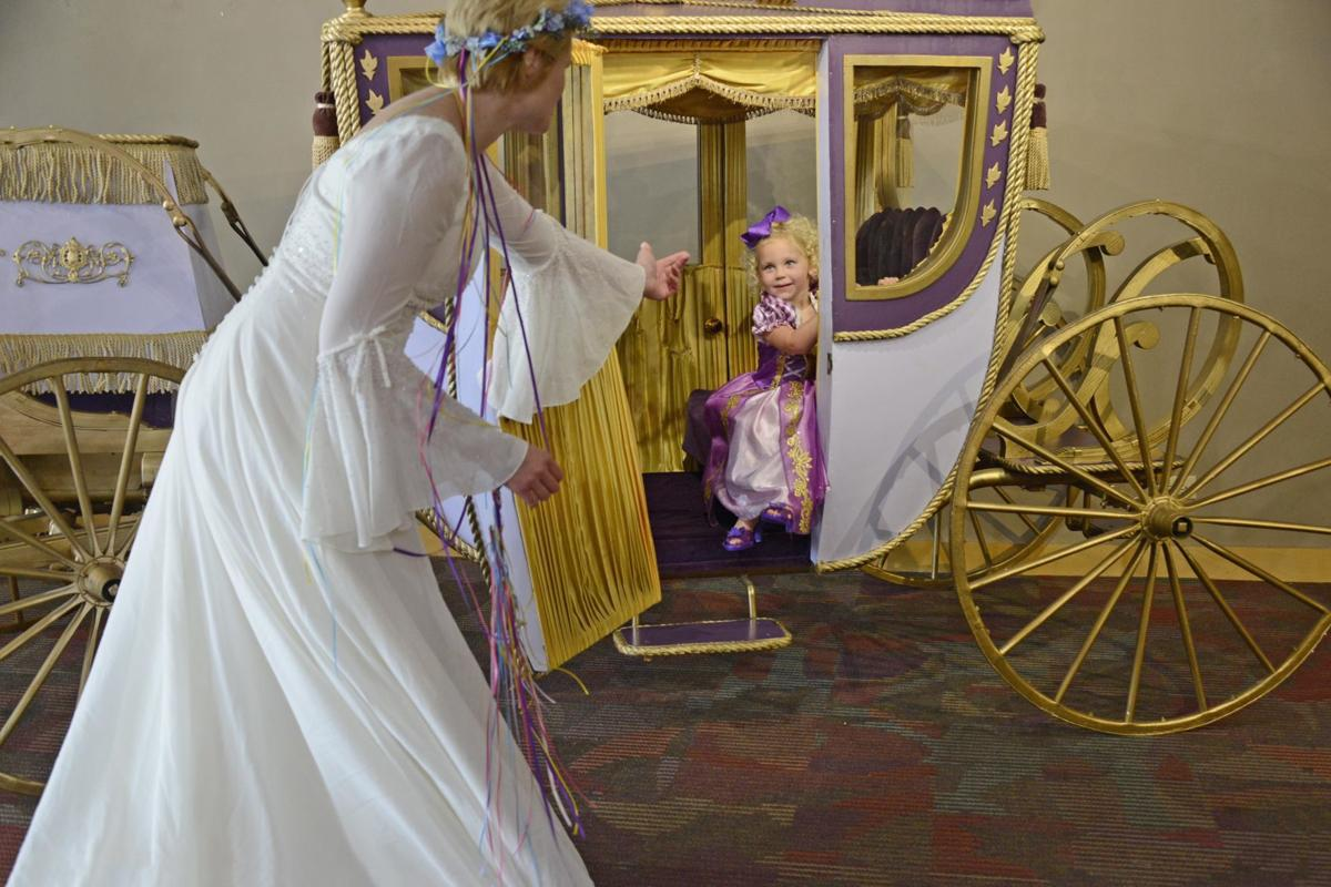 Fairy Godmother helps young child from Cinderella carriage