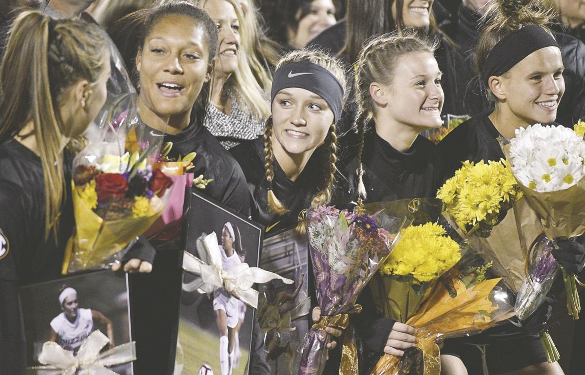 Anna Frick, Peyton Joseph, Sarah Luebbert, Izzy Coulter, and Madison Lewis smile and hold flowers
