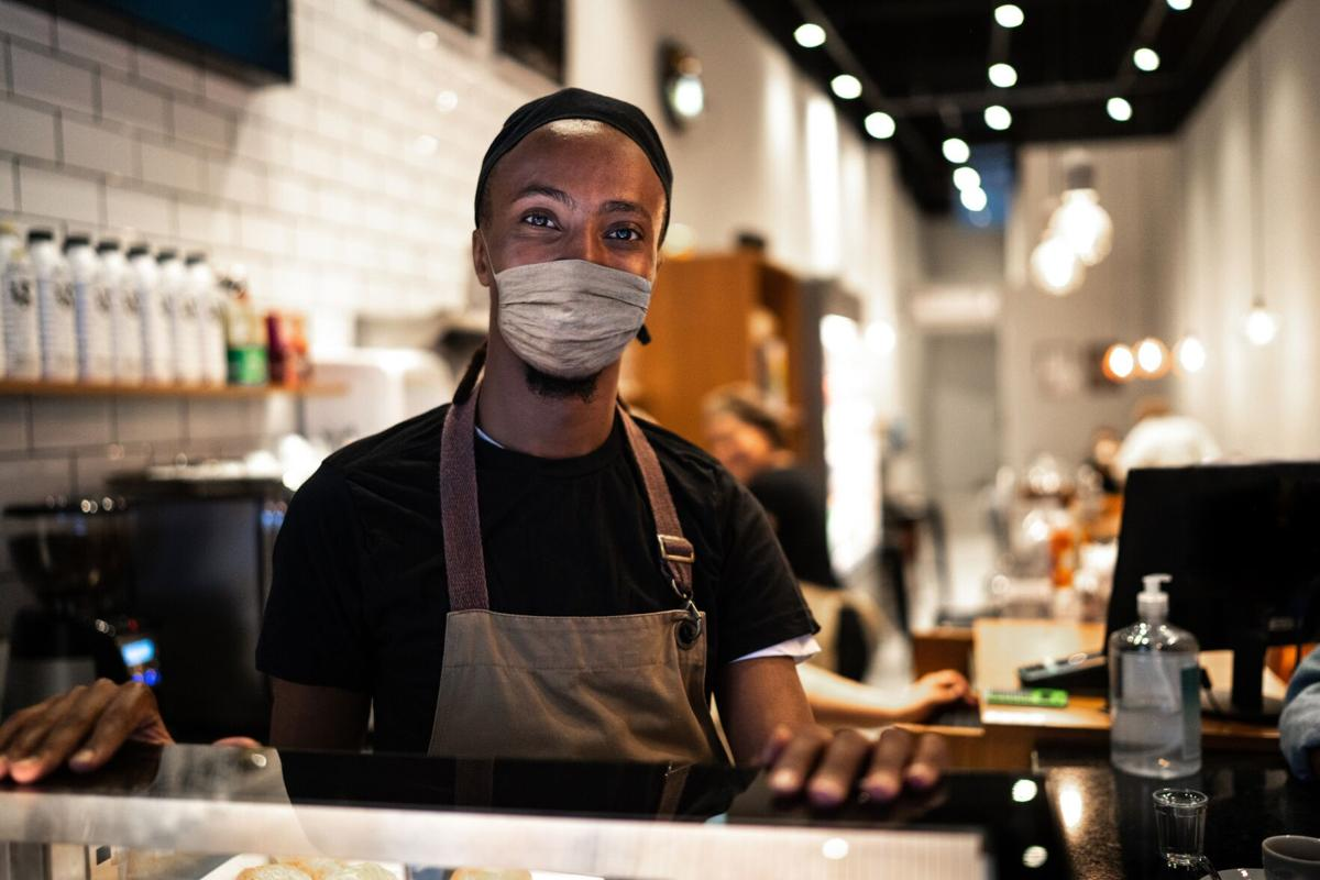 Portrait of young waiter with face mask in coffee shop
