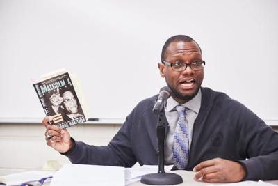 Dr. Charles Watson holding a book on Malcom X while discussing Pan-Africanism during a recent forum at the Minneapolis Community and Technical College.