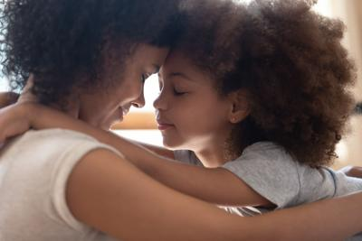 Mixed race mother touching foreheads with little cute daughter