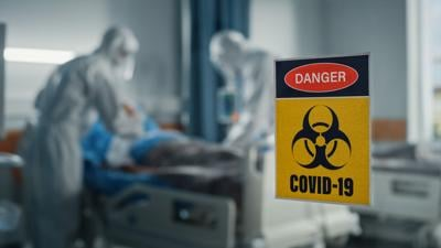Hospital Coronavirus Emergency Department Ward: Doctors wearing Coveralls, Face Masks Treat, Cure and Save Lives of Patients. Focus on Biohazard Sign on Door, Background Blurred Out of Focus