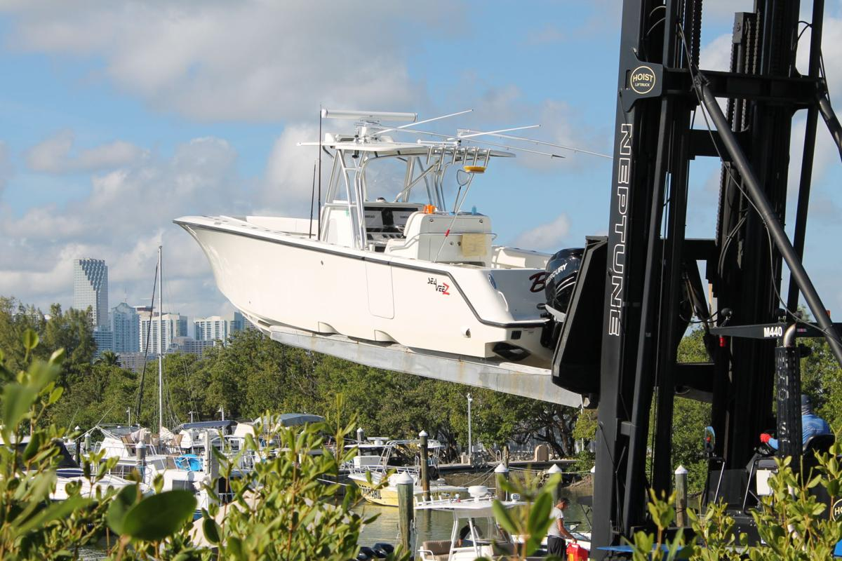 A recreational boat is brought down for the client by the Neptune Hoist Liftruck operator at Rickenbacker Marina.