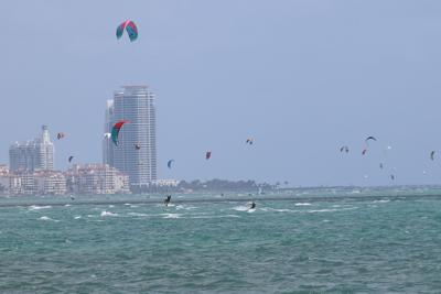 Kite Surfers Practice Their Sport Against The Backdrop Of City Miami Skyline