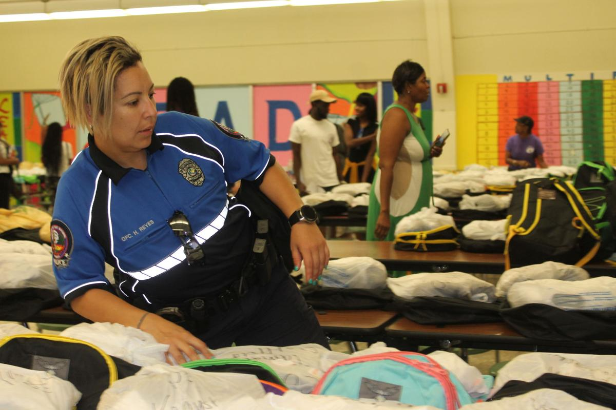 Key Biscayne Officer Hilda Reyes maneuvers around to find a student's book bag and school supplies.