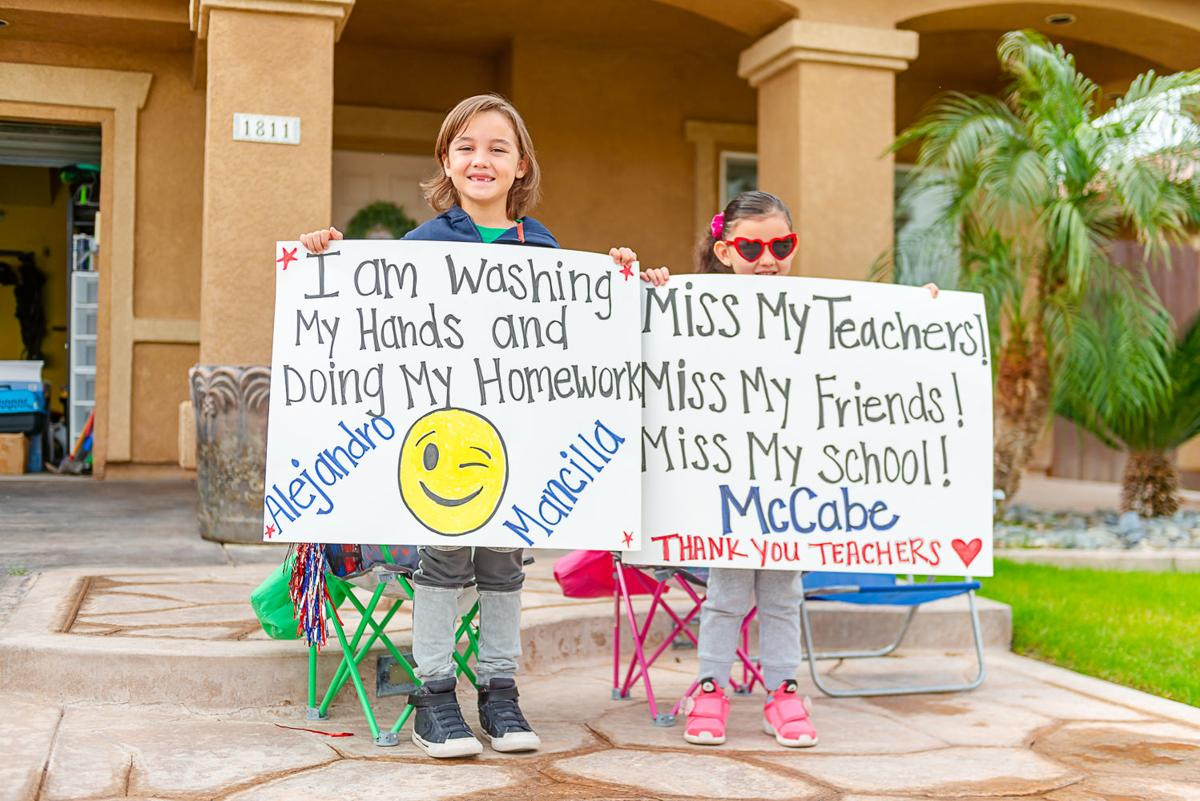 Two schools pay their students a visit with drive-by parades