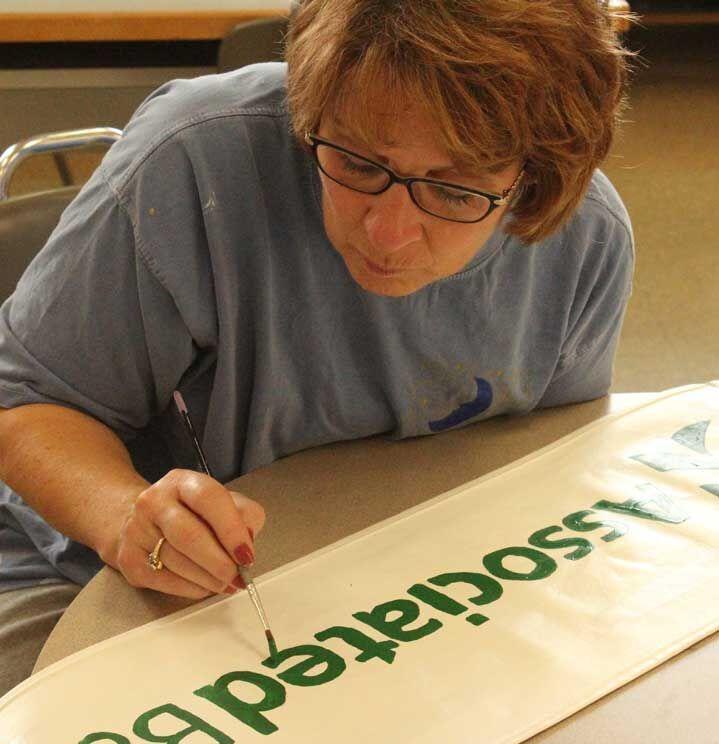 Kiel River Walk District's volunteers paint banners