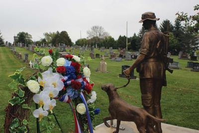 A statue of the late Leo Meyer and his British-trained Labrador retriever Bruce now stands watch over the cemetery in Johnsburg.