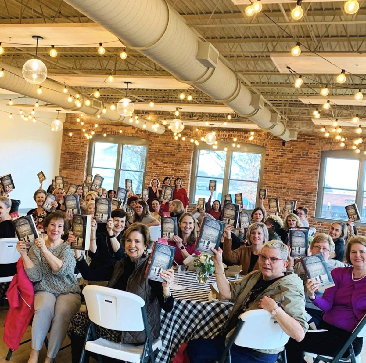 Readers and fans raise their books to say thank you to the staff of Story on the Square.  The authors, are in the background copy.jpg