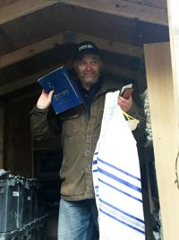 <p>Ruben Arquilevich, executive director of URJ Camp Newman, examines religious supplies that survived the fire despite widespread destruction.</p>