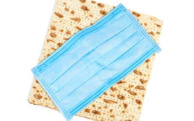 Coronavirus pandemic. Passover matzo and protective face mask on white background, top view