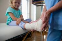 <p>Physiotherapist putting bandage on injured feet of girl patient in clinic</p>