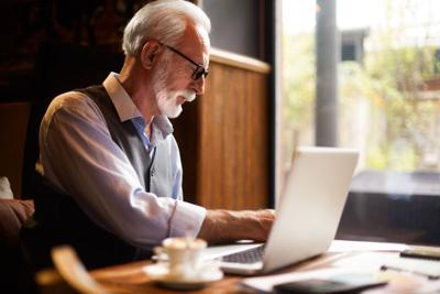 Elderly manager working on his laptop in a cafeteria with a cup of coffee on the table next to him