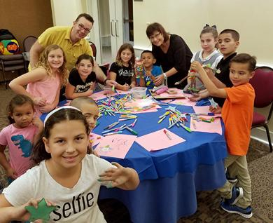 <p>Temple Chai Cantor Ross Wolman and Temple Chai Religious School Principal of Hebrew Studies Ariela Ben-Dor (standing in back) join the synagogue's children in entertaining their young Family Promise of Greater Phoenix guests.</p>