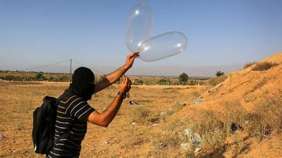 <p>Palestinians in Gaza attach a balloon to flammable materials to be flown towards Israel. These incendiary devices have caused destruction to trees, animals, the land and the environment. June 17, 2018.</p>