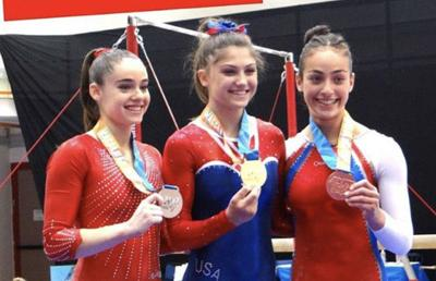 <p>Evelyn Micco, center, won gold in the uneven bars.</p>